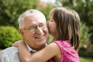 A little girl leaning over to whisper secrets in her grandfather's ear as he smiles in delight. Better hearing makes listening fun.
